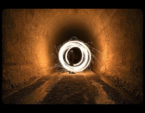 long-exposure photograph of circular light trails in a tunnel
